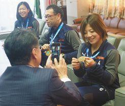 高見優莉子選手(右端)と金メダルの写真を撮る村椿晃市長(手前)=魚津市役所で