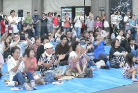 湯布院映画祭の前夜祭を楽しむ来場者=22日、由布市湯布院町のJR由布院駅前
