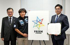 福岡県久留米市で発足した女子ラグビーチームのロゴを掲げる「ナナイロプリズム福岡」GM兼選手で7人制女子日本代表の中村知春(中央)ら