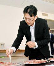 試食会で「チョコブリ」の見た目や味を確かめる参加者=19日午前、宇和島市下波