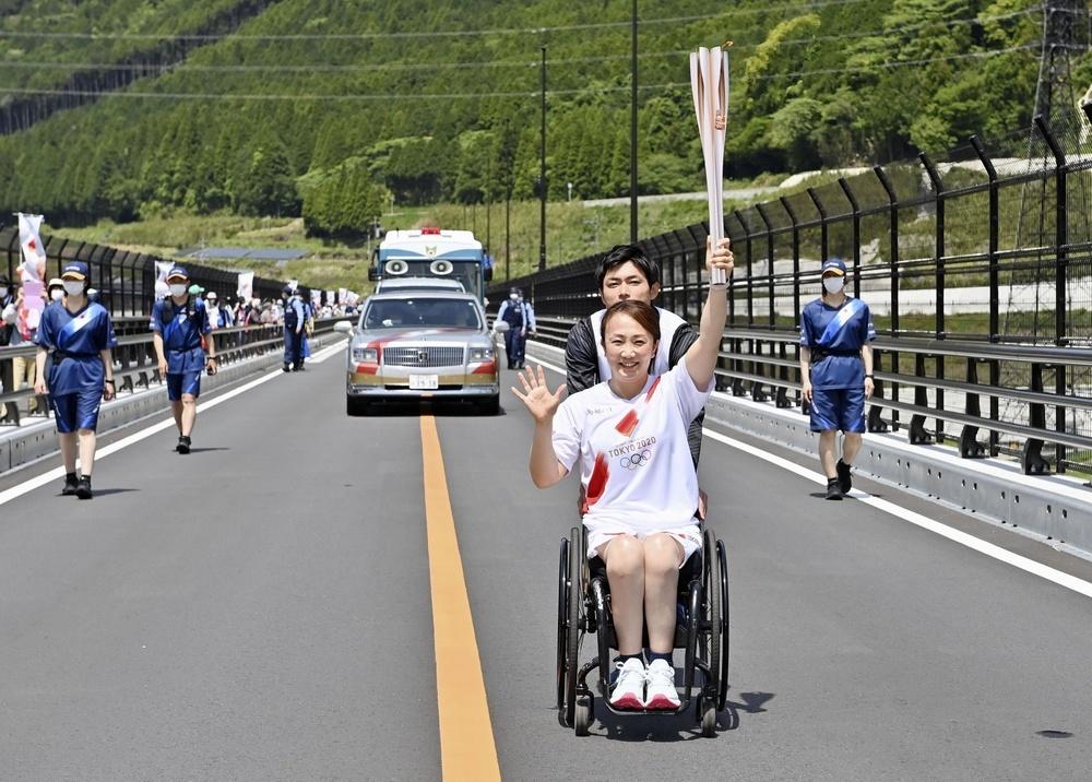 熊本日日新聞代表撮影、新阿蘇大橋で聖火ランナーを務めた中尾有沙さん=6日午前、熊本県南阿蘇村