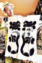 復刻シャツ「魚河岸ビンテージ」を手にする川合優基さん=22日、焼津市