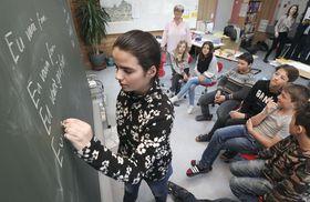 スイス・グラウビュンデン州フタンの小学校で行われているロマンシュ語の授業。クリスティーナ(手前)がつづる言葉を子どもたちが見守る=4月(共同)