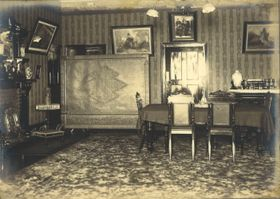 昭和初期に撮影したとみられる旧グラバー住宅「大食堂」の古写真。天井の照明器具の奥に「長州ファイブ」の写真が飾られている(グラバー園提供)
