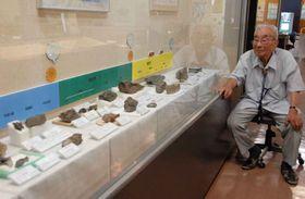 地元で採取した古生代から新生代までの化石に見入る吉井さん(夜久野町化石・郷土資料館)=福知山市夜久野町平野