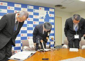西日本豪雨時の高知市幹部の競馬旅行で処分を発表し、頭を下げる岡﨑市長=中央=ら(20日午前、同市役所)