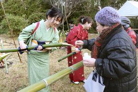 奈良市の大安寺で開かれた「笹酒祭り」で、参拝客に日本酒を振る舞う「笹娘」=23日
