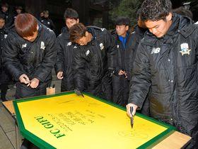 必勝祈願後、J2復帰への願いを込め、大きな絵馬にサインを書き入れるFC岐阜の選手たち=岐阜市伊奈波通、伊奈波神社