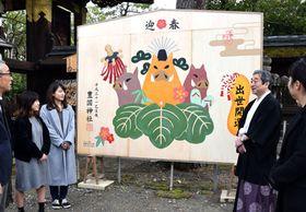 愛らしいイノシシの大絵馬を見上げる学生ら(京都市東山区・豊国神社)