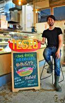 投票者に「リバティ・ドッグ」を振る舞うTESIO店主の嶺井大地さん=14日、沖縄市の同店
