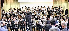 顧問の酒井澄人さんの指揮に合わせて息の合った演奏を披露する部員とエキストラの参加者