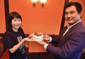 小谷公仁子事務局長(左)にホールケーキを手渡す内藤浩一社長=姫路市西八代町