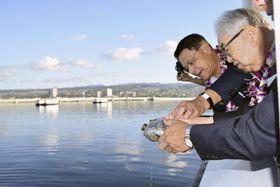 米兵遺品の水筒から海にバーボンを注ぎ犠牲者を供養する菅野寛也さん(右端)=6日、米ハワイ州・真珠湾(共同)