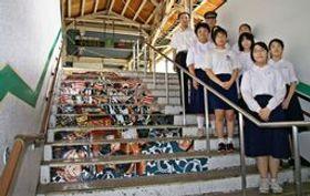 JR新発田駅に飾られた新発田まつりの階段アートと、制作した本丸中生徒ら=新発田市諏訪町1