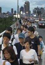 6月、大阪府北部地震で公共交通機関が運転見合わせとなり、新淀川大橋を歩いて渡る大勢の人たち