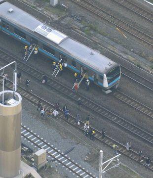 架線が断線したトラブルで、停車したJR京浜東北線の車両から降り線路を歩く乗客=16日午後、神奈川県川崎市(共同通信社ヘリから)