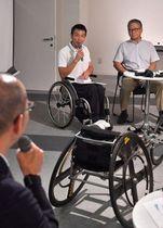 競技用車いすを前にして語る室塚さん(奥側左)と森田さん(同右)