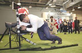 ラグビーW杯のファンゾーンに設置された、タックルの強さを計測する装置。手前は元日本代表の畠山健介氏=19日午後、東京・有楽町