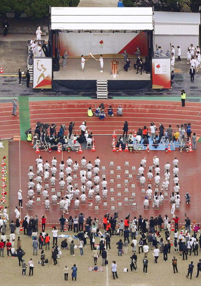 福岡県全域で聖火リレーの公道走行が中止となり、一般客の入場を規制して福岡市の平和台陸上競技場で開かれた点火セレモニー=11日午後(共同通信社ヘリから)