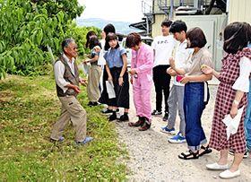 平井社長(左)から畑の説明を受ける学生ら