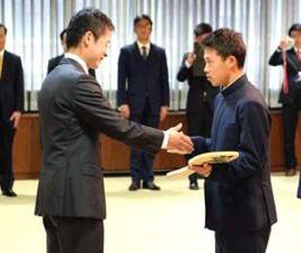 湯崎知事(左)からしゃもじを贈られ、激励される佐々木主将