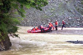 流された後、対岸の崖にしがみついたキャンプ客を助けようと懸命に行われた県警や消防、自衛隊による救助活動=山北町の玄倉川(1999年8月15日撮影)