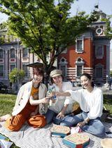好天に恵まれた大阪市中央公会堂の前でピクニックを楽しむ女性たち=20日午後