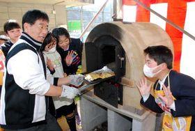 焼き上がったピザを石窯から取り出す野地校長。児童からは歓声が上がった