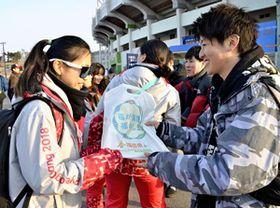 ボランティアとの交流で赤べこなど本県をPRする学生(右)