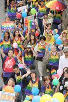 LGBTの啓発パレードで、シンボルカラーのファッションを身にまとい行進する人たち=2017年5月、東京都渋谷区