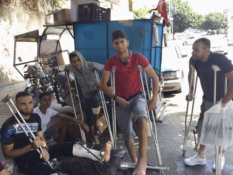 パレスチナ自治区ガザで、イスラエルへの抗議デモに参加し、脚に銃撃を受けた若者ら=8月28日(共同)