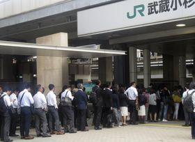 構内が浸水した川崎市のJR武蔵小杉駅で入場が規制され、列に並ぶ利用客ら=15日午前