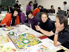 人生ゲームのルールなどを確認する商店街店主ら(四万十市役所)