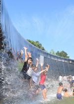 梅雨明けした県内で水遊びに歓声を上げる子どもたち=20日、滝沢市鵜飼