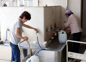 浄泉寺でポリタンクに水をくむ市民たち