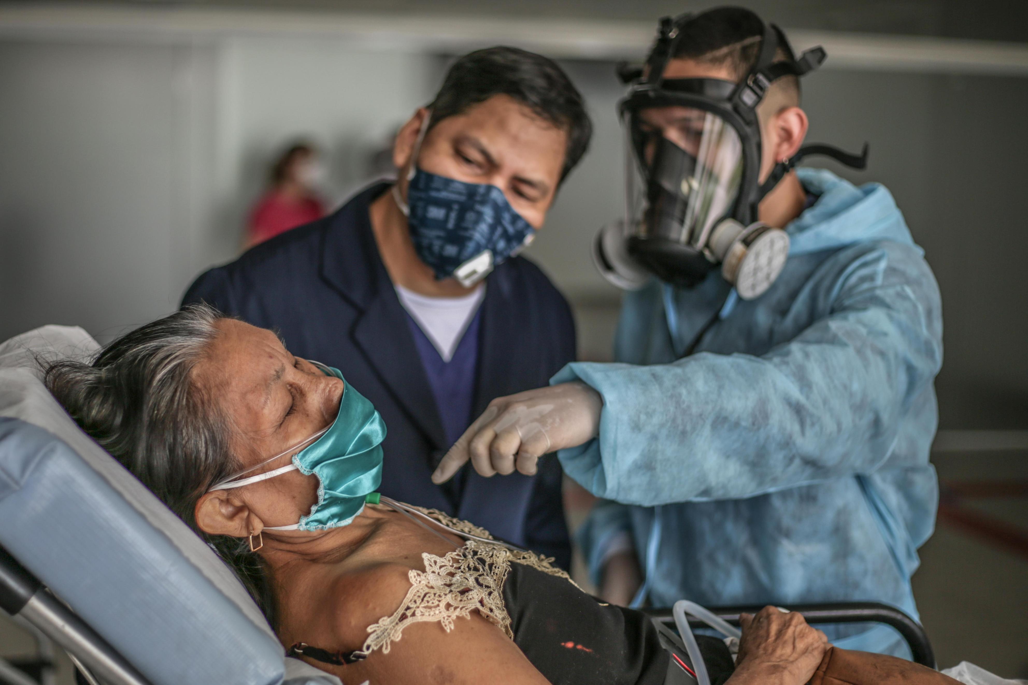 27日、ブラジル北部マナウスで、新型コロナウイルスに感染した女性(手前)を診察する医師と看護師(ゲッティ=共同)