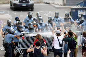 米ミネソタ州ミネアポリスで、デモ参加者に催涙ガスを使用する警官隊=27日(ロイター=共同)