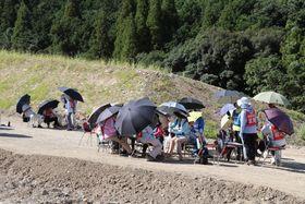 石木ダム建設に反対し、県道の付け替え道路で座り込みをする地権者ら=川棚町