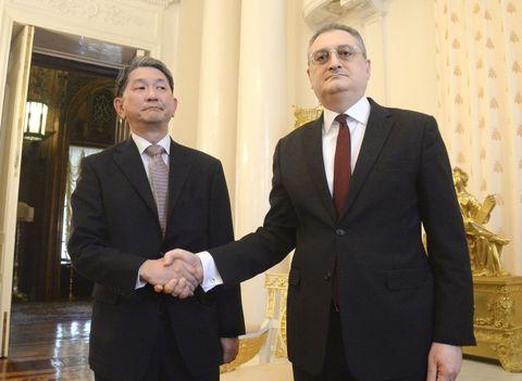 21日、モスクワでロシアのモルグロフ外務次官(右)と握手する森健良外務審議官(共同)