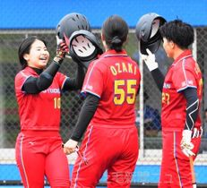 NEC―太陽誘電 3回裏誘電1死、ソロ本塁打を放った山本(左)を尾崎と藤田が迎え、祝福のメットタッチ=高崎市ソフトボール場