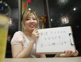 筆談で接客するホステスとして働く粟田さん=札幌市のススキノ