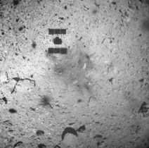 はやぶさ2が着陸し、上昇を始めた直後に高度30メートル以下で撮影したりゅうぐうの表面。中央左上にはやぶさ2の影が映り、黒く見えるのは噴射で舞い上がった砂とみられる(JAXA提供)
