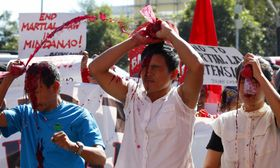 フィリピン南部ミンダナオ島での戒厳令下での人権弾圧に対し、抗議する人々=12日、マニラ(AP=共同)