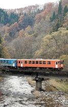 紅葉が残る山並みを背景に走る秋田内陸線の列車