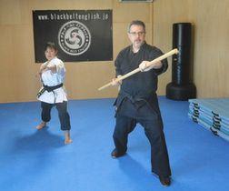 棒を使った空手の形を披露するロバートさん(右)と妻の智恵さん=彦根市東沼波町で