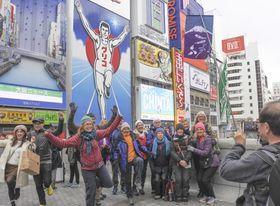 大阪・ミナミの名所、グリコの看板前でポーズを取る訪日観光客ら