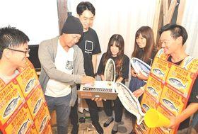 クラウドファンディングの目標額達成を確認するプロジェクトメンバー=焼津市
