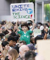 地球温暖化に対する大人の危機感が低すぎると訴える集会でプラカードを掲げる少年=20日午後、東京都渋谷区