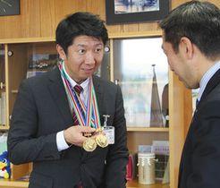 影山剛士市長に二つのメダルを見せる山本光文さん=湖西市役所で