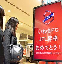 いわきFCのJFL昇格を祝う電子看板を眺める高校生=5日午後、いわき市・ラトブ
